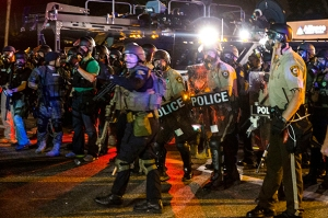 A line of police officers yells at a crowd of rowdy demonstrators during further protests in reaction to the shooting of Michael Brown near Ferguson, Missouri